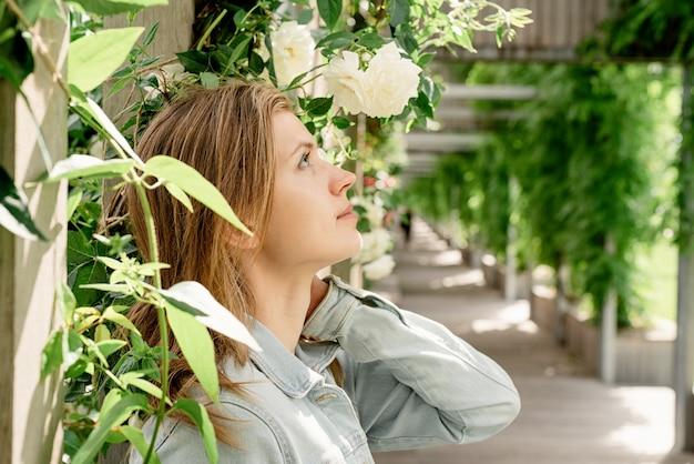 目をそらしている庭や公園で白いバラに立っている美しい若いブロンドの女性