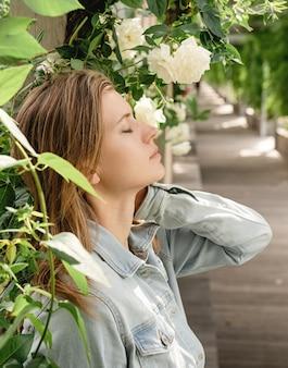 目を閉じて庭や公園の白いバラに立っている美しい若いブロンドの女性