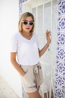 Bella giovane donna bionda in piedi al muro ricoperto di azulejo piastrelle tradizionali portoghesi.