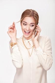 전화 통화하는 아름 다운 젊은 금발 여자와 그녀의 머리와 재생. 놀라움과 기쁨