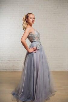 灰色の壁にパステルベージュのドレスのパンの厄介な髪の美しい若いブロンドの女性