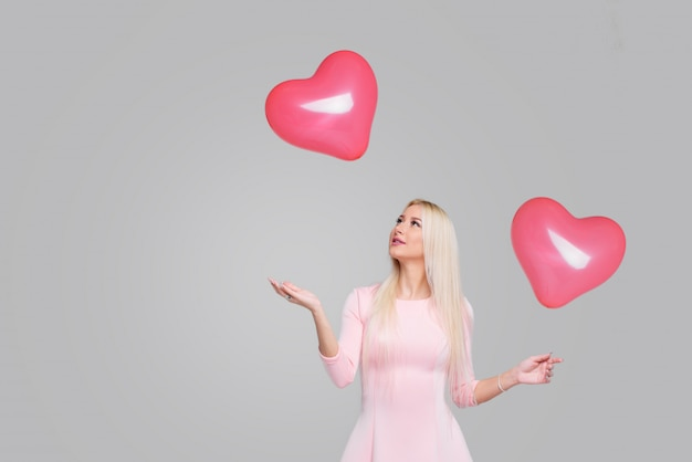 Beautiful young blond woman with pink heart shape air balloon on grey . woman on valentine's day. symbol of love - image. space for text