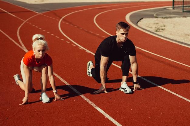 Красивая молодая блондинка и парень готовятся к бегу