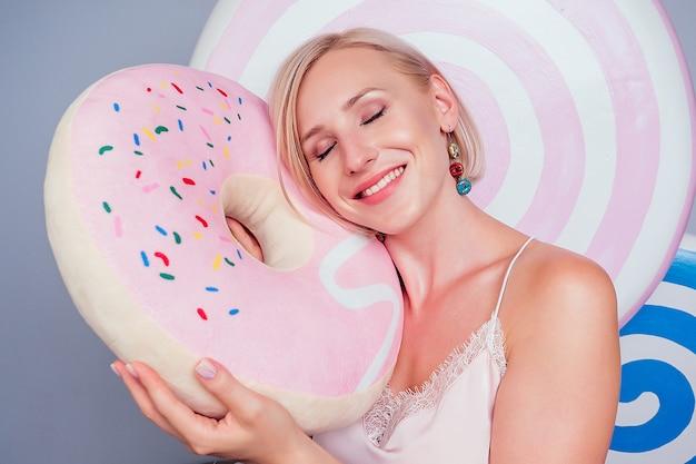 美しい若いブロンドのバービー眠そうな女性菓子屋セクシーなモデルは、巨大なピンクのドーナツを抱きしめ、シルクのパジャマの背景の柔らかい枕の上で眠るスタジオショットの偽のスイーツロリポップキャンディー。甘い夢のダイエット