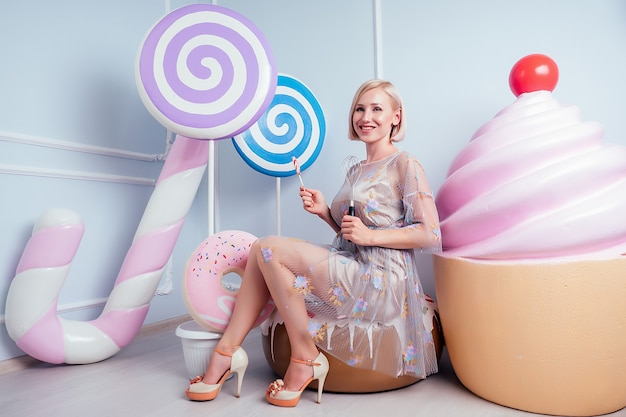 Beautiful young blonde barbie sweet woman confectioner sexy model perfect makeup hold lollipop and confectionery whisk background fake sweets candy huge cake in studio shot. diet and weight loss