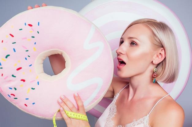 美しい若いブロンドのバービー甘い女性菓子屋セクシーなモデル完璧なメイクは、スタジオショットで測定テープの背景偽のお菓子キャンディー巨大なロリポップでピンクのドーナツを保持します。ダイエットと減量