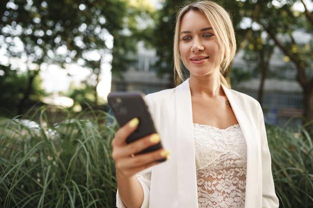 도시에서 스마트폰을 사용하는 아름다운 젊은 금발 사업가