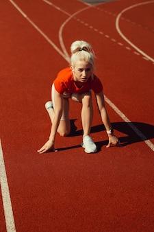 Красивая молодая блондинка готовится бежать