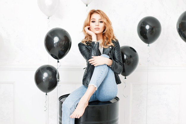 Beautiful young blonde girl in a black leather jacket and blue jeans sits near balloons
