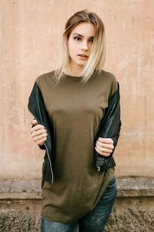 빈 녹색 티셔츠와 가죽 재킷에 아름 다운 젊은 금발 소녀