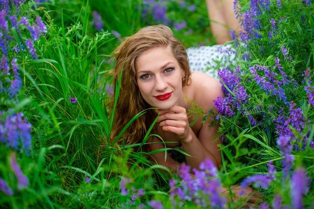 紫色の野花に囲まれた緑の野原で美しい若いブロンドの女の子。野生動物の美しい少女。