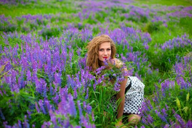 Красивая молодая блондинка в зеленом поле среди фиолетовых полевых цветов.