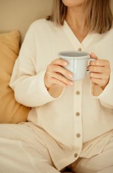 Красивая молодая блондинка в пижаме, держа чашку чая, сидя в белых постельных принадлежностях и
