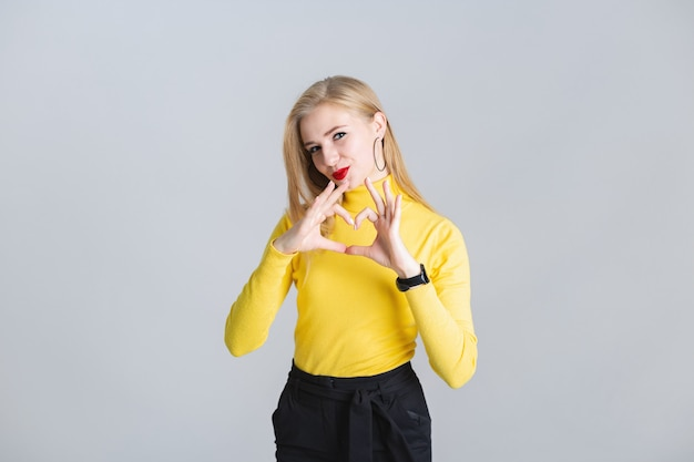 Beautiful young blonde girl shows gesture heart with her hands