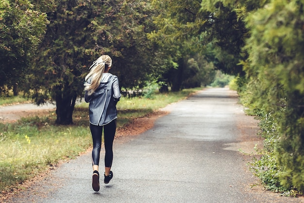 Beautiful young blonde girl with long hair is running in a park at rainy day,