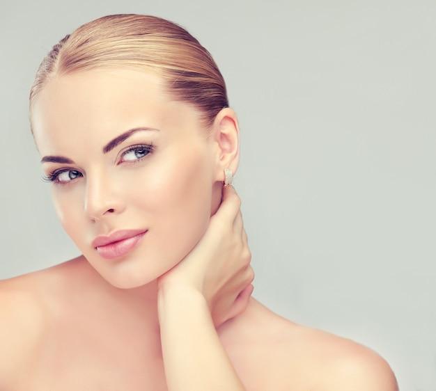 きれいな新鮮な肌を持つ美しい、若い、ブロンドの髪の女性が首に触れています。やわらかいメイクと髪の毛が房に集まっています。フェイシャルトリートメント、美容、美容技術、スパ。