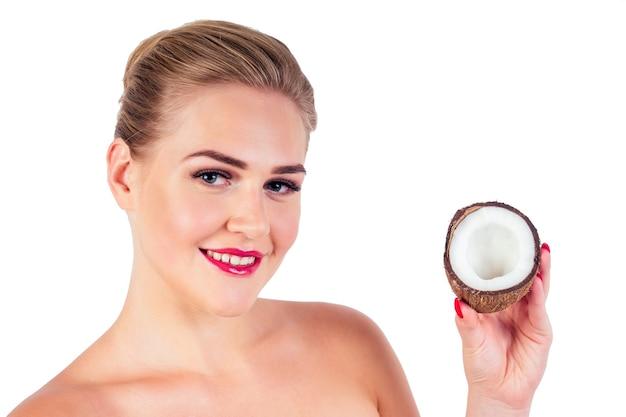 긴 속눈썹을 가진 아름다운 금발 헤어스타일 소녀는 입술에 빨간 립스틱을 바르고 흰색 배경에 있는 스튜디오에서 코코넛을 손에 든 완벽한 피부를 가지고 있습니다. 아름다움 얼굴입니다.