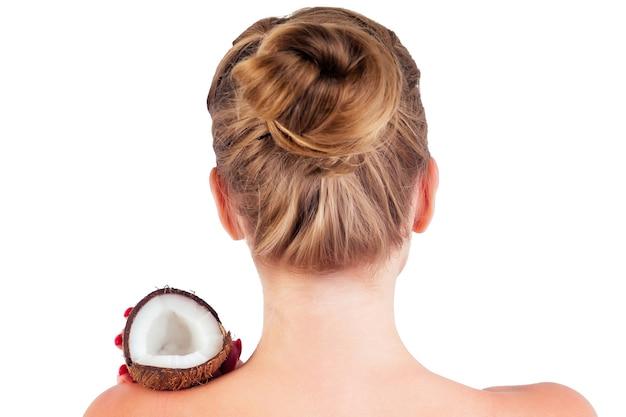 그녀의 손 어깨에 코코넛을 가진 아름 다운 젊은 금발 헤어스타일 소녀 흰색 배경에 스튜디오에서 맨 손으로 맨 뒤. 미용 & 헤어.