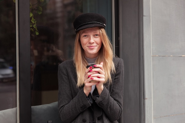 街を歩きながら外でコーヒーを飲む赤いマニキュアを持つ美しい若いブロンドの女性、カフェの外観の上にポーズをとってエレガントな服を着て