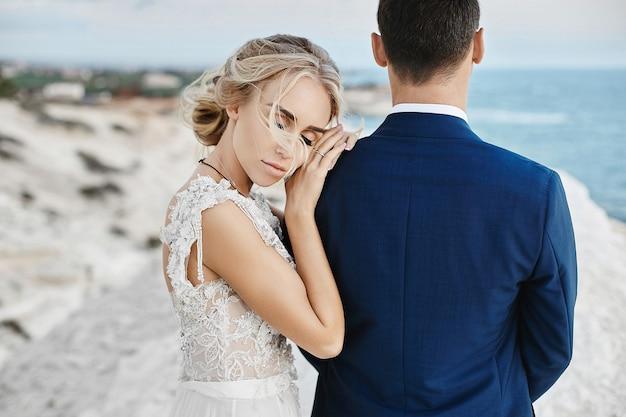 유행 흰색 레이스 드레스에서 아름 다운 젊은 금발 모델 여자는 세련 된 파란색 정장에 잘 생긴 남자에 기대어 아드리아 해 연안에서 흰 바위에 포즈