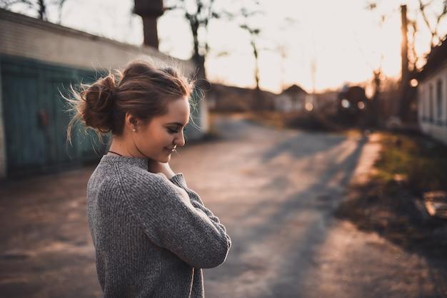 美しい若いブロンドのモデルの女の子の笑顔。グレーのニットセーター。日没時。肖像画。お団子で結んだ髪