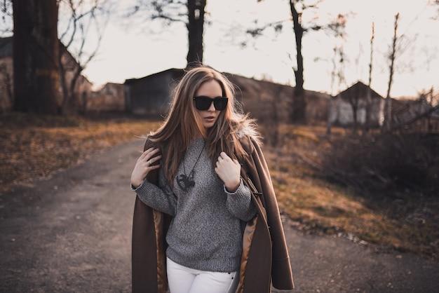 美しい若いブロンドのモデルの女の子。白いズボン。グレーのニットセーター。黒いブーツ。黒のサングラス。馬の形をした首の木製ペンダント。茶色のコートでポーズ。日没時。ポートレート