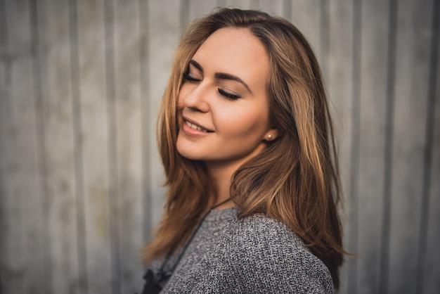 目を閉じて笑顔の美しい若いブロンドモデルの女の子。グレーのニットセーター。日没時。肖像画。