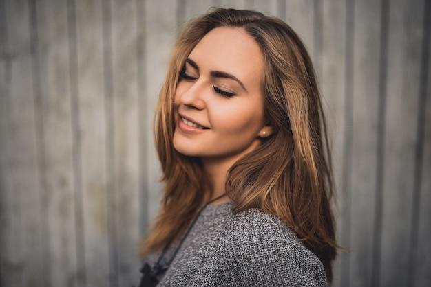 目を閉じて笑顔の美しい若いブロンドモデルの女の子。グレーのニットセーター