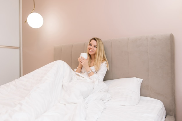 Beautiful young blonde smiling girl with coffee in a white bed, good morning