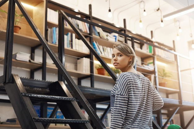 Beautiful young blonde student girl with short hair in casual striped shirt spending time in modern library after university, preparing for exams with friends. girl standing near stairs going to take