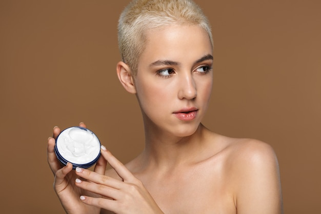 A beautiful young blonde stylish woman with short haircut posing isolated over dark beige wall wall holding cream.
