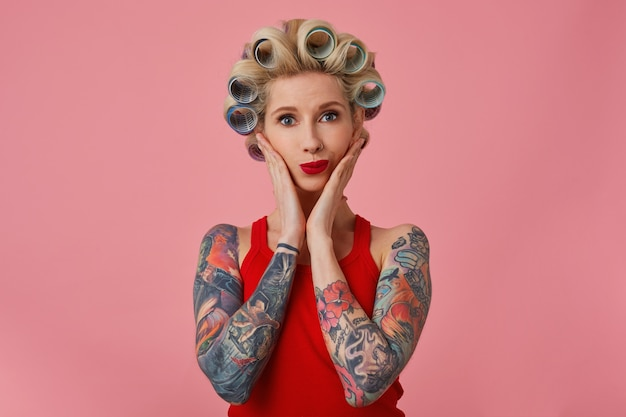 Beautiful young blonde tattooed lady with red lips holding her face with palms and looking positively at camera, having curlers on her head and preparing for going out, isolated over pink background