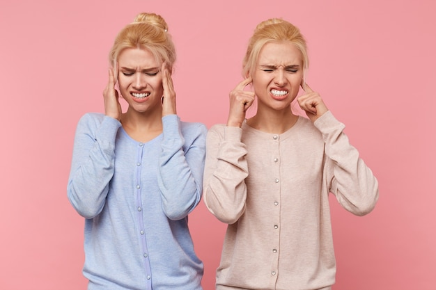 Beautiful young blonde twins experience discomfort, pain in temples and tinnitus isolated over pink background.