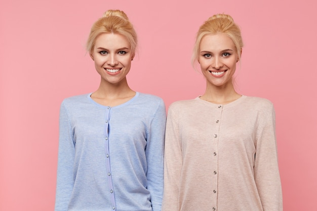 Beautiful young blonde twins in a good mood, broadly smiling in the camera isolated over pink background.