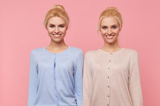 ピンクの背景の上に隔離されたカメラで広く笑って、良い気分で美しい若いブロンドの双子。