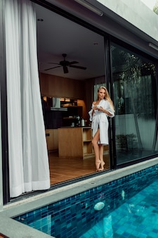 Beautiful young blonde woman in bathrobe holding cup of coffee near pool in her villa