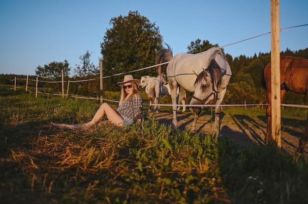 아름 다운 젊은 금발의 여자는 모자에 사파리 스타일을 입고 순종과 함께 포즈를 취하는 격자 무늬 셔츠