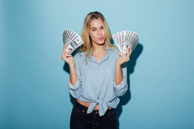 Beautiful young blonde woman holding money in hands