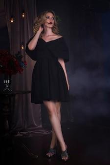 할로윈 메이크업과 피 묻은 얼굴 예술, 빈티지 인테리어와 검은 드레스에 아름 다운 젊은 금발의 여자