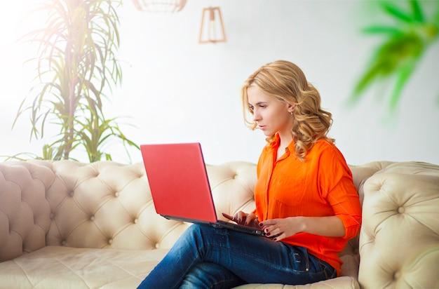 カジュアルな服装の美しい若いブロンドの女性は自宅のソファの上のラップトップで働いています。