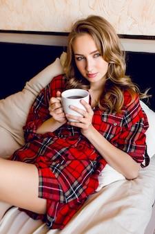 赤い市松模様のシャツを着た美しい若いブロンドの女性は、午前中に彼女のベッドでリラックスし、お茶を飲みながら夢を見ています。