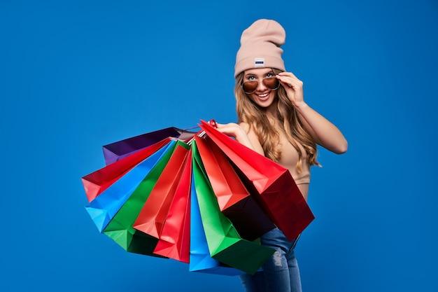 販売中のパッケージとサングラスと帽子の美しい若いブロンドの女性