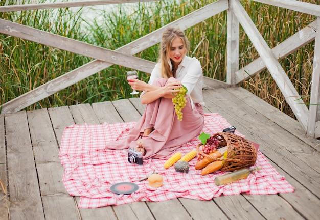 木製の桟橋だけでピクニックを持つヴィンテージのレトロな服で美しい若いブロンドの女性。フレンチスタイルの屋外のピクニック