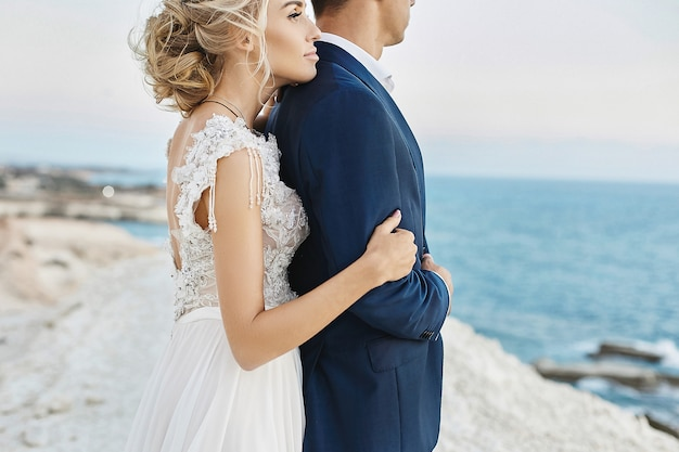 흰색 레이스 드레스에 아름 다운 젊은 금발 여자는 아드리아 해 연안에 하얀 바위에 세련 된 파란색 정장에 잘 생긴 남자에 기댄 다. 세련 된 신랑 웨딩 드레스에서 모델 여자