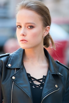 Beautiful young blonde woman in a leather jacket outdoor
