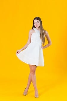 Beautiful young blonde woman in nice spring dress, posing on yellow background in studio