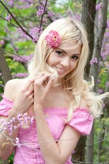 Beautiful young blonde woman outdoor portrait in spring park near sakura tree