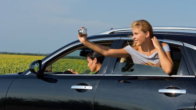 Beautiful young blonde woman passenger leaning out of car window taking a photograph of herself