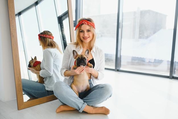 Красивая молодая блондинка женщина, играя со своей собакой дома, улыбаясь. счастье.