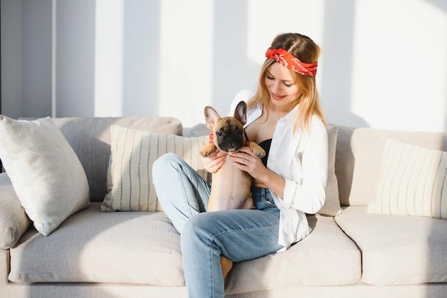 Красивая молодая блондинка женщина играет со своей собакой дома, улыбаясь